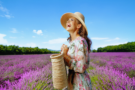 happy elegant woman in long dress with straw bag looking into the distance against lavender field of Provence, France. Superb traveling photos at France's most beloved attractions - lavender field