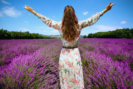 Seen from behind modern woman in lavender field in Provence, France rejoicing. Provence attractions. scenic plateau.tourist-friendly region. authentic agritourism in Provence in July Stock Photo