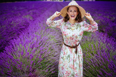 Portrait of happy trendy woman in summer dress at lavender field in Provence, France in straw hat. First unforgettable journey on the Valensole plateau to world of magical flowering lavender fields Stok Fotoğraf