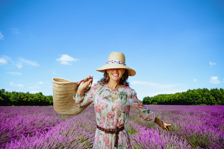 trendy woman in floral dress with straw bag rejoicing at lavender field in Provence, France. Woman tourist find perfect lavender field traveling by roads in Provence. Blue summer sky and warm sunshine