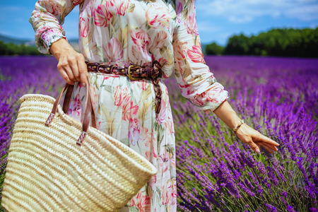 Closeup on modern woman in summer dress with straw bag touching lavender against lavender field of Provence, France. Unforgettable atmosphere of purple lavender flowers in Provence