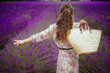 Seen from behind elegant woman in summer dress with straw bag rejoicing against lavender field of Provence, France. An unforgettable inspiring trip to Provence in the summer