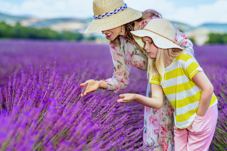 modern mother and daughter touching lavender against lavender field of Provence, France. Lavender can soothe headaches. what else can we learn during time spent as agritourists in Provence?