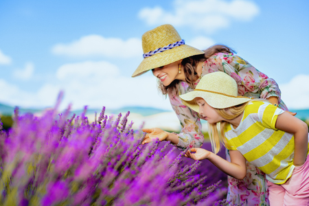 young mother and child in lavender field in Provence, France smelling lavender - Provence's undoubted rural highlights. mother and child in straw hats enjoying scent of a lavender field