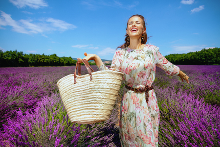 happy trendy woman in long dress with straw bag rejoicing against lavender field of Provence, France. Excited woman traveller happy to visit beautiful blue lavender in bloom of Valensole plateau