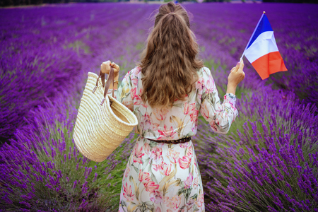 Seen from behind modern woman in summer dress with straw bag and French flag at lavender field in Provence, France. Woman tourist enjoying Provencal summer