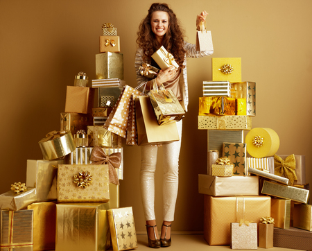 Full length portrait of happy young woman in gold beige clothes with gifts and shopping bags showing small shopping bag among 2 piles of golden gifts in front of a plain wall. holidays shopping