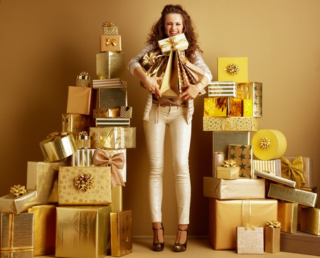 Full length portrait of happy trendy fashion-monger in gold beige clothes among 2 piles of golden gifts in front of a plain wall barely holding gifts and shopping bags. abundance of gifts for everyone