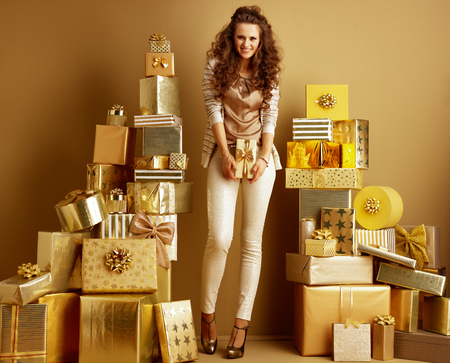 Full length portrait of happy trendy fashion-monger in gold beige clothes among 2 piles of golden gifts in front of a plain wall holding gift box. holidays shopping illustration. efficiency shopping