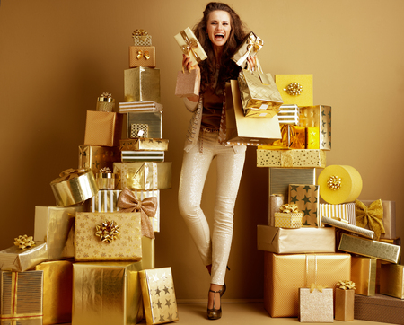 Full length portrait of happy stylish woman in gold beige clothes with gifts and shopping bags among 2 piles of golden gifts in front of a plain wall. concept of abundance of gifts for everyone.