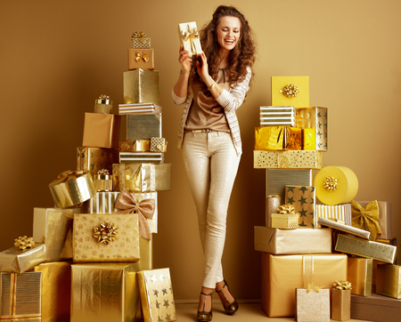 Full length portrait of happy elegant woman in gold beige clothes among 2 piles of golden gifts in front of a plain wall shaking present box to know what inside. holidays shopping illustration. Stock Photo