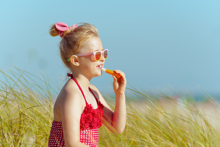 trendy girl in red swimwear applying lipstick with spf on the ocean coast. protect your hair from sun, heat, and humidity before heading to the beach. wild beach with green grass and no people.