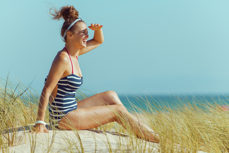 happy modern woman in striped swimsuit looking into the distance while sitting on the seashore. quiet vacation heaven. blue sky. 版權商用圖片