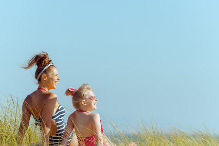 smiling young mother and daughter in swimwear on the seashore looking aside. quiet vacation heaven. protect your hair from sun, heat, and humidity before heading to the beach. blond hair child.