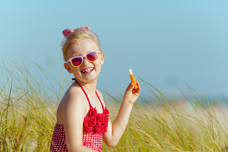 Portrait of trendy girl in red swimsuit holding lipstick with spf on the ocean shore. sunny summer midday. spending hours at the beach. blond hair |child in red dotted swimsuit with flowers