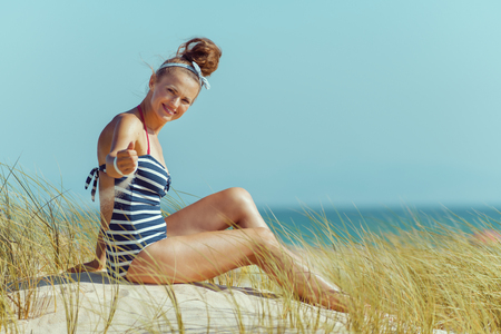 smiling modern woman in striped beachwear playing with sand on the seashore. carefree beach fun. protect your hair from sun, heat, and humidity before heading to the beach.