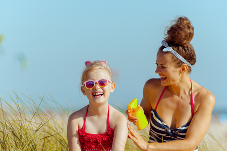 happy young mother and child in beachwear on the ocean coast applying SPF. sunscreen hight SPF with broad range UV UVB for maximum sunburn protection.