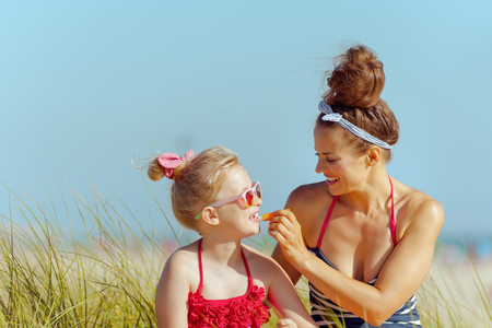 smiling modern mother and daughter in swimwear applying lipstick with spf on the ocean coast. lip balm with SPF sun protection to combat dry lips. Sun protected hair. minimal to no crowd peace. Archivio Fotografico - 115163049