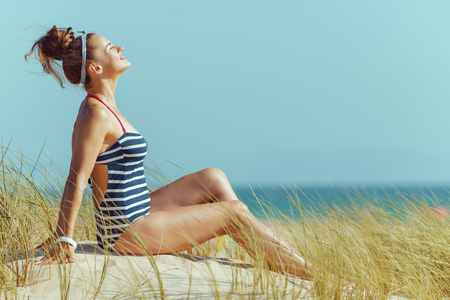 relaxed modern woman in striped swimsuit sitting on the seacoast. total relaxation on the best beach vocation. protect your hair from sun, heat, and humidity before heading to the beach. blue sky. Banque d'images - 115163065