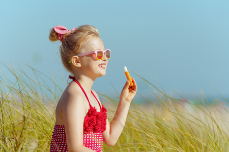 trendy child in red swimsuit looking into the distance while holding lipstick with spf on the ocean shore. sunny summer midday. 版權商用圖片 - 115163360