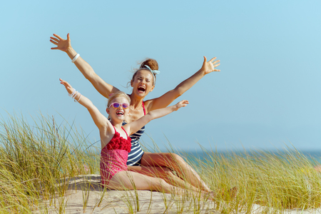 happy modern mother and child in beachwear on the beach rejoicing. getting vitamin D after long winter months. modern сaucasian mother 30 something years old in white blue striped swimsuit brunette.