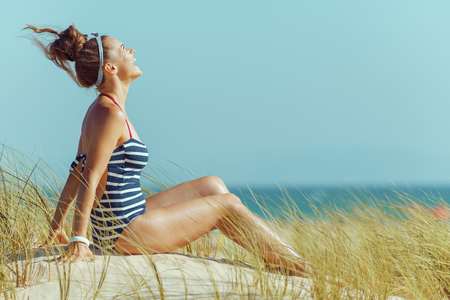 smiling modern woman in striped beachwear on the seashore relaxing. bun hairstyle. Sunny summer midday. blue sky. protect your hair from sun, heat, and humidity before heading to the beach.
