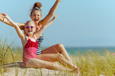 happy young mother and child in swimwear on the beach rejoicing. sunny summer midday. protect your hair from sun, heat, and humidity before heading to the beach.