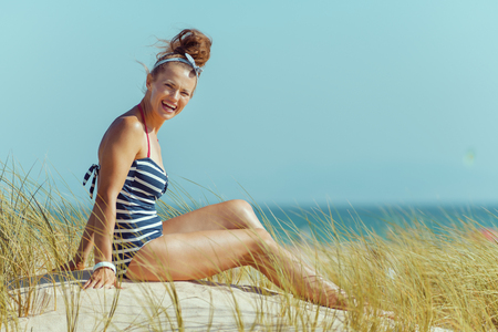 Portrait of happy young woman in striped swimsuit sitting on the seashore. carefree beach fun. european woman brunette 30 something years old. bun hairstyle. wild beach with green grass and no people