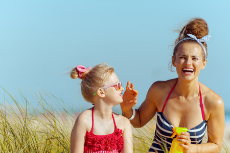 smiling modern mother and child in beachwear on the beach applying SPF. sunscreen hight SPF with broad range UV UVB for maximum sunburn protection. Stock Photo - 115163419