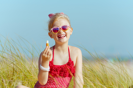 Portrait of modern girl in red swimwear holding lipstick with spf on the beach. sunny summer midday. minimal to no crowd peace. blond hair daughter wearing sunglasses.