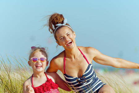 smiling modern mother and child in swimwear on the beach having fun time. protect your hair from sun, heat, and humidity before heading to the beach. minimal to no crowd peace. blond hair child.