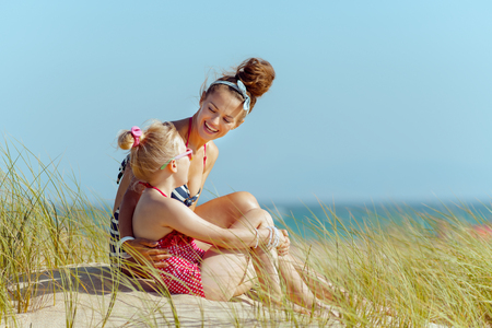 smiling young mother and child in beachwear on the seashore looking at each other. getting vitamin D after long winter months. blond hair daughter in red dotted swimsuit with flowers. Stock Photo