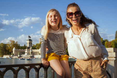 Portrait of happy trendy mother and child tourists at El Retiro Park in Madrid, Spain. Madrid is the sunny capital of Spain. one of global travellers preferred destination. child sitting on fence
