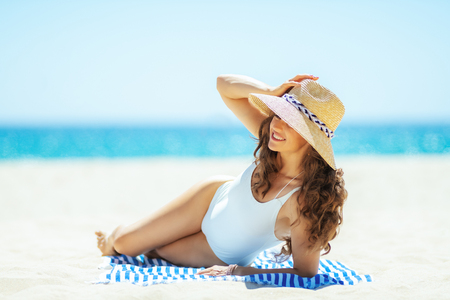 smiling modern woman in white swimwear on the ocean shore looking into the distance while laying on a striped towel. woman wearing straw hat. Covering up with a hat to avoiding the harsh summer midday. Stock Photo