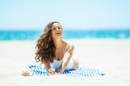 smiling modern woman in white swimsuit on the ocean shore lying on a striped towel enjoying. stressed free beach retreat. Sunny summer midday. Stock Photo