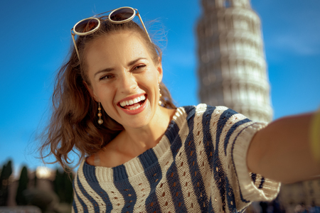 happy trendy woman in striped blouse in the front of leaning tower in Pisa, Italy taking selfie. classic example of overtourism. european woman brunette ponytail hairstyle 30 something years old. Stockfoto