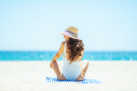 Seen from behind modern woman in white swimwear looking aside while sitting on a striped towel on the beach. woman wearing straw hat. Sunny summer midday. getting vitamin D after long winter months.