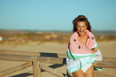 smiling young woman in beachwear on the ocean coast in the evening wrapped in watermelon towel. european woman brunette 30 something years old standing near wooden fence. blue sky. carefree fun