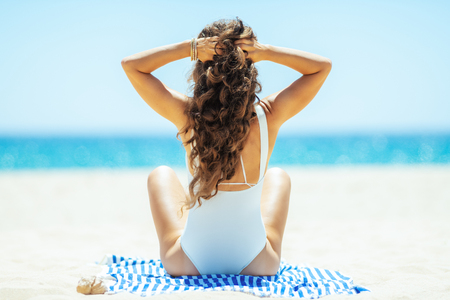 Seen from behind healthy woman in white swimwear on the ocean shore siting on a striped towel. Sun protected hair. spending hours at the beach. 写真素材 - 115931374