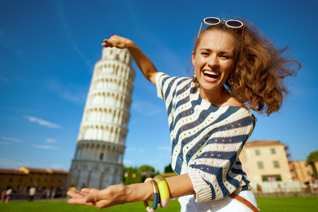 smiling stylish woman in striped blouse posing for travel photos against leaning tower in Pisa, Italy. I'm here and I need to take stereotypical tourist photos. having micro trip. сaucasian woman.