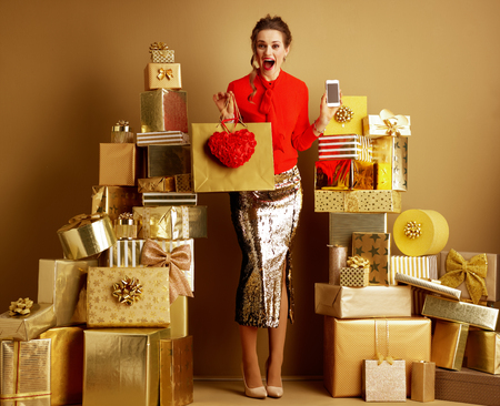 Full length portrait of excited stylish shopper woman in red blouse and golden sparkly sequin pencil skirt with shopping bag, red heart and smartphone among 2 piles of golden gifts. Valentine's Day.