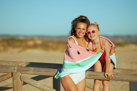 Portrait of smiling modern mother and child in swimwear on the ocean coast in the evening wrapped in watermelon towel. mother and daughter hugging near wooden fence. minimal to no crowd peace.