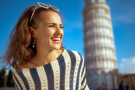 happy elegant woman in striped blouse near leaning tower in Pisa, Italy looking into the distance. Sunny summer midday. having micro holidays. tour operators top choice. �aucasian woman. blue sky. Stockfoto