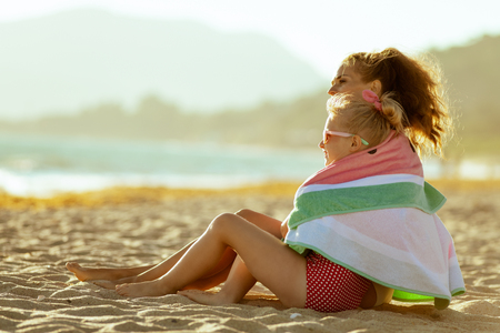 modern mother and daughter in swimwear on the seashore in the evening looking into the distance wrapped in watermelon towel. minimal to no crowd peace. modern european mother. summer evening. Stock Photo