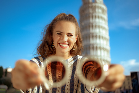 smiling trendy woman in striped blouse in the front of leaning tower in Pisa, Italy showing sunglasses. european woman with brown hair ponytail hairstyle 30 something years old. having micro trip.