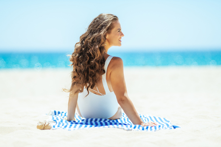 happy fit woman in white swimwear on the seashore siting on a striped towel and looking aside. quiet vacation heaven. protect your hair from sun, heat, and humidity before heading to the beach.