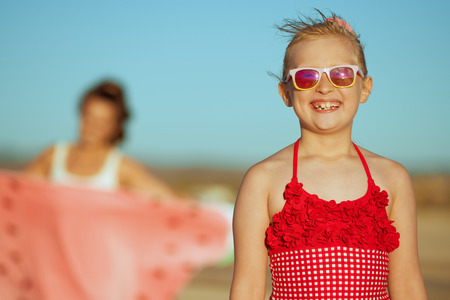 happy girl and mother in background on the ocean shore in the evening. protect your hair from sun, heat, and humidity before heading to the beach. minimal to no crowd peace. blond hair girl.