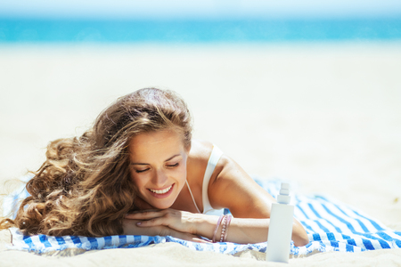 relaxed trendy woman in white swimwear with sun block laying on a striped towel on the seashore. sunscreen SPF or bug repellent or insect bite remedy or hair protection leave-in SPF conditioner.