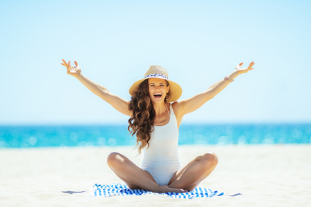 smiling trendy woman in white beachwear on the ocean shore rejoicing while sitting on a striped towel. woman in straw hat. minimal to no crowd peace. getting vitamin D after long winter months.
