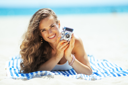 smiling healthy woman in white swimsuit with retro photo camera laying on a striped towel on the seacoast. share beach vacation with family and friends and on social media platforms. Foto de archivo - 115931596
